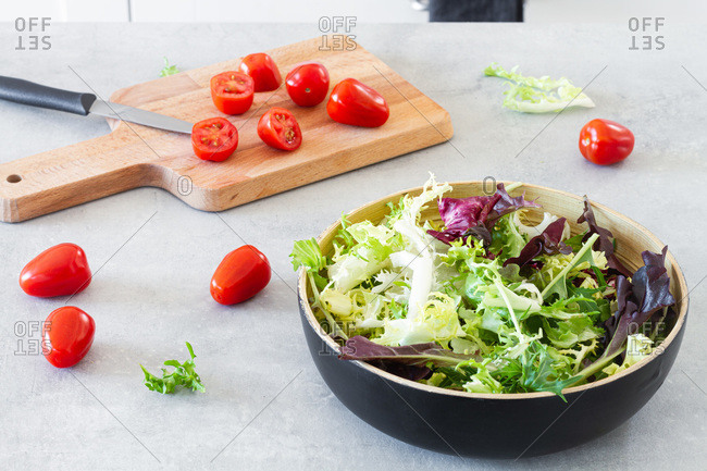 Salad green leaves in bowl placed in table with fresh tomatoes