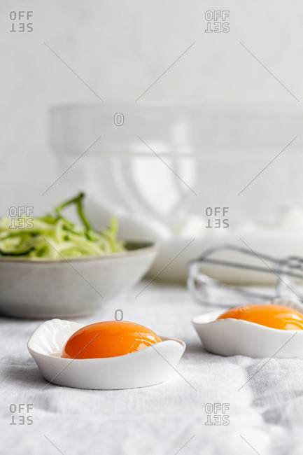 Ceramic bowls with separated raw egg yolks placed on table with fresh greens and mixer during breakfast preparation