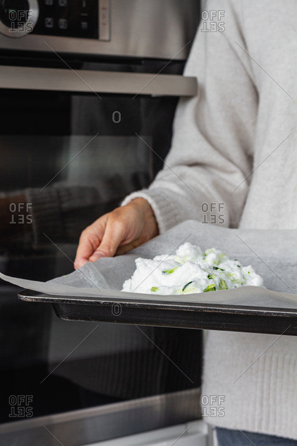 Crop unrecognizable person standing near oven and holding baking tray with whipped egg whites mixed with green vegetables while preparing cloud eggs for breakfast