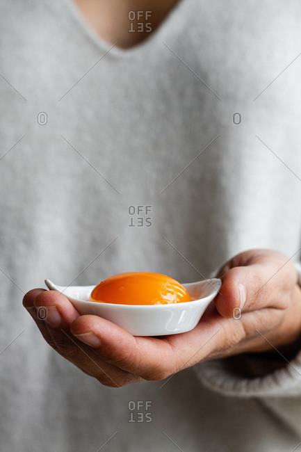 Crop anonymous person holding small ceramic bowl with raw egg yolk while preparing healthy breakfast