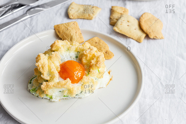 High angle of appetizing homemade baked cloud eggs with green vegetables served with crispy crackers for healthy breakfast
