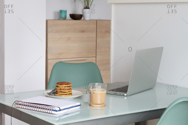 Empty table with laptop and notepad near prepare coffee and biscuits in light kitchen at home