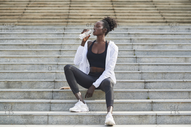 Relaxed African American female runner sitting on stairs in city and drinking fresh water during training
