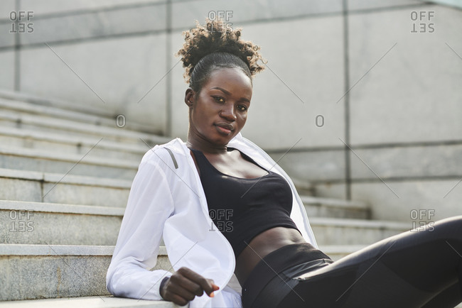 Confident African American female runner sitting on stone stairs on street while relaxing during workout and looking at camera