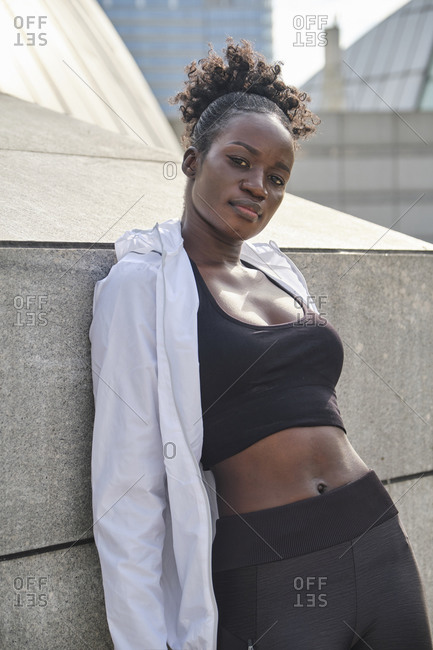 Fit African American sportswoman leaning on stone construction in city and looking at camera