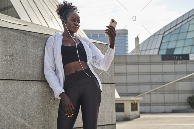Slim African American female athlete standing on street on sunny day and messaging on mobile phone while having break during workout