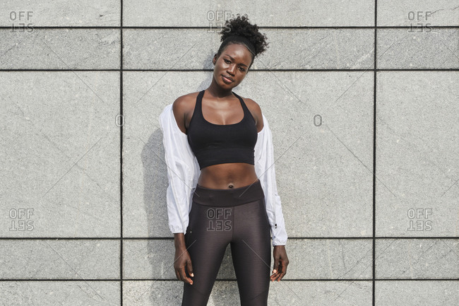 Fit African American female athlete standing on concrete wall on the street while resting after workout looking at camera