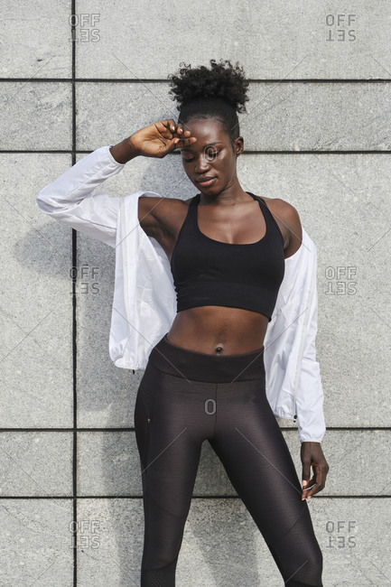 Fit African American female athlete standing on concrete wall on the street while resting after workout looking down