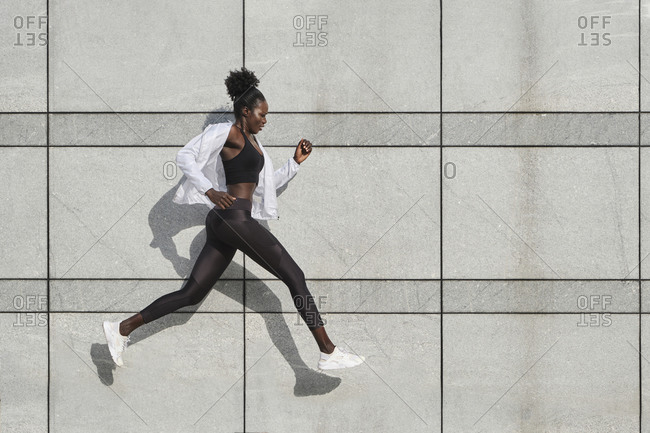 Side view of fit African American female athlete jumping above ground on street while doing exercises during workout
