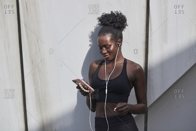 Smiling confident black female athlete in earphones listening to songs on mobile phone while standing on the street on sunny day