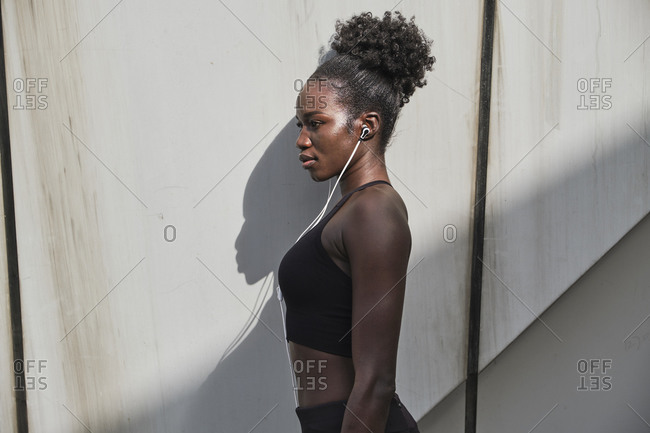 Side view of confident black female athlete in earphones listening to songs on street on sunny day
