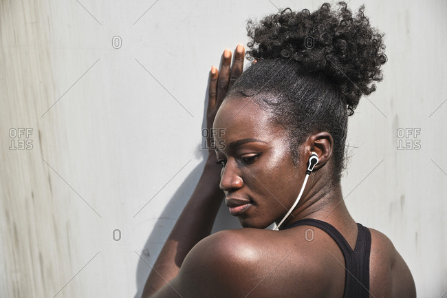 Confident black female athlete in earphones listening to songs on street on sunny day