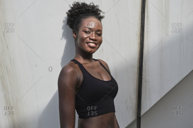 Cheerful African American female athlete wearing sports bra leaning on stone wall of building and looking at camera