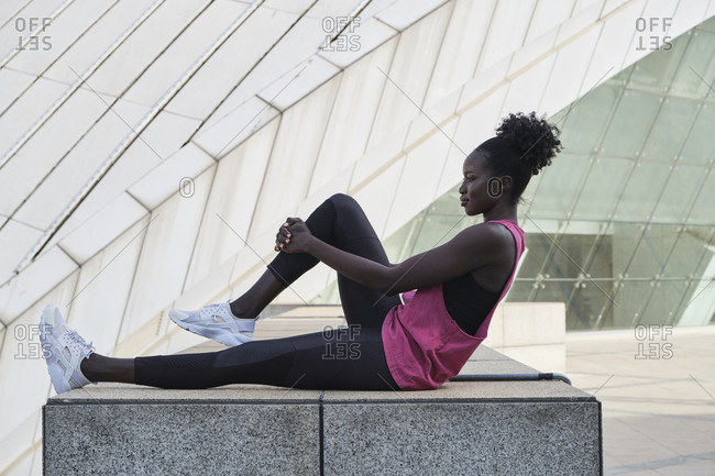 Side view of concentrated black female runner sitting on stone border and stretching legs while warming up before training in city