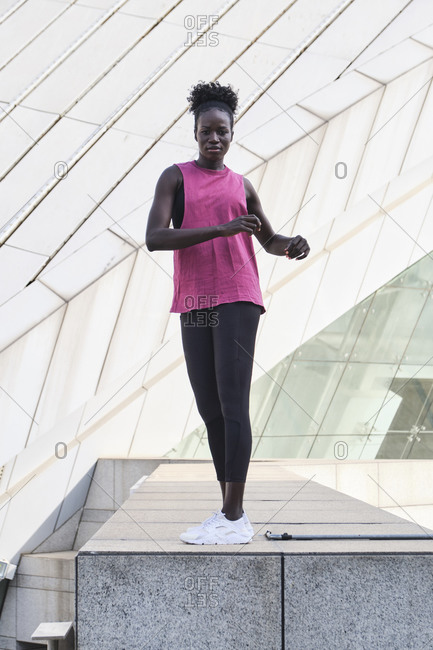Side view of focused black female athlete in sportswear doing exercises while stretching and warming up in city