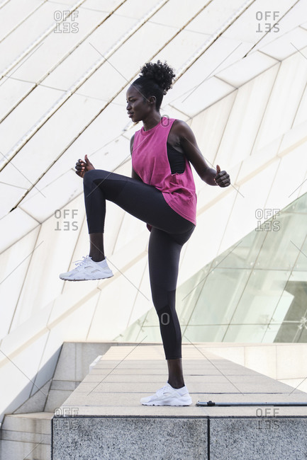 Side view of focused black female athlete in sportswear doing exercises while stretching and warming up legs in city