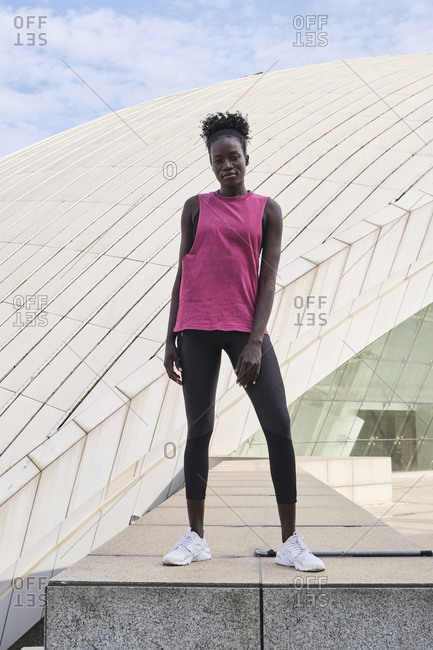 Confident African American female athlete in activewear standing on street and looking at camera while having break during workout