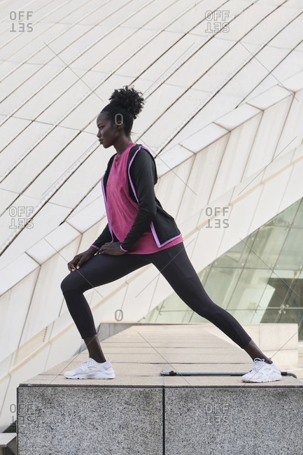 Side view of determined African American female athlete in activewear doing side lunges and stretching legs during training on street while looking away