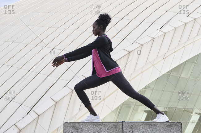 Side view of focused African American sportswoman doing lunges with raised arms while stretching legs during workout in city