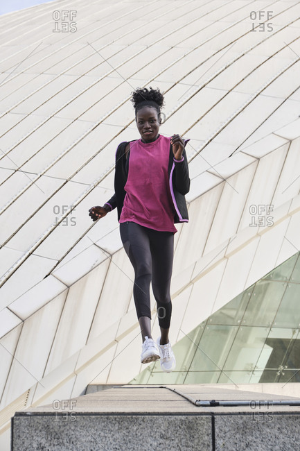 Focused black female athlete in sportswear doing exercises while jumping in city