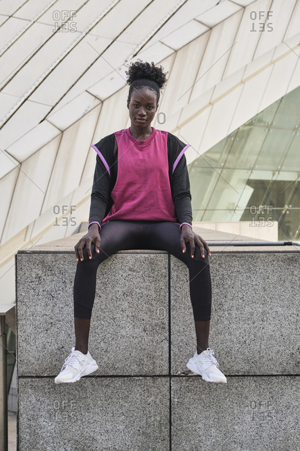 Determined African American female athlete in sportswear sitting on street and looking at camera