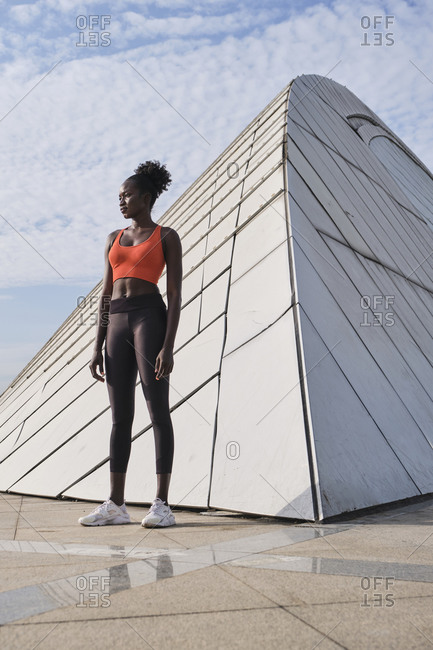 Confident African American sportswoman with slim body standing near geometric construction in city and looking away