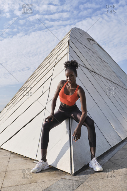 Confident African American sportswoman with slim body sitting on geometric construction in city and looking at camera