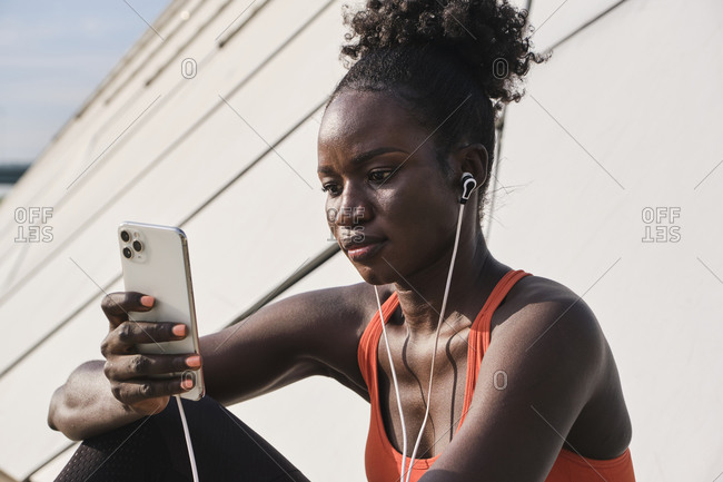 Calm African American athletic female sitting on street and listening to songs in earphones while chatting on social media via smartphone