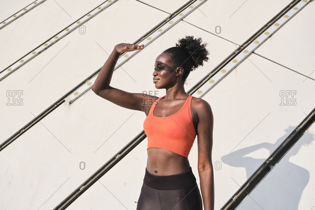 Cheerful ethnic fit female in sportswear standing on street and covering face from sunlight while looking away