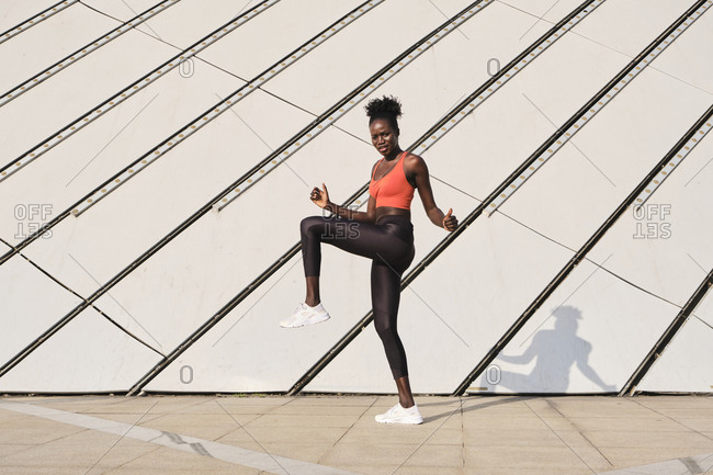 Side view of focused ethnic sportswoman doing exercises and warming up legs while looking at camera during dynamic workout