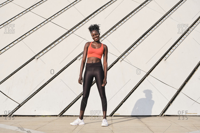 Smiling African American female athlete in sportswear standing in urban area in city looking at camera