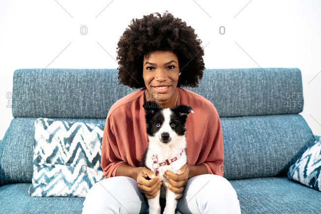 Cheerful African American curly haired female with cute little dog sitting on sofa and looking at camera while resting at home