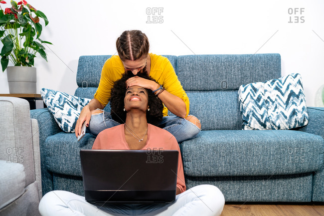Happy young multiracial homosexual women enjoying weekend together while spending time with laptop and smartphone in living room