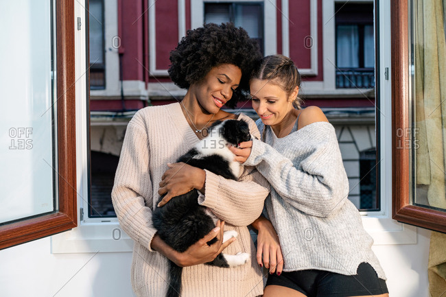 Positive young multiracial lesbian girlfriends caressing cute little puppy while standing near window at home