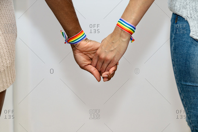 Unrecognizable crop multiracial lesbian couple with rainbow bracelets holding hands on white background