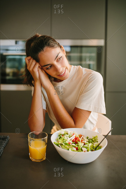 Peaceful female leaning on hands and sitting at table with glass of orange juice and bowl of vegetable salad