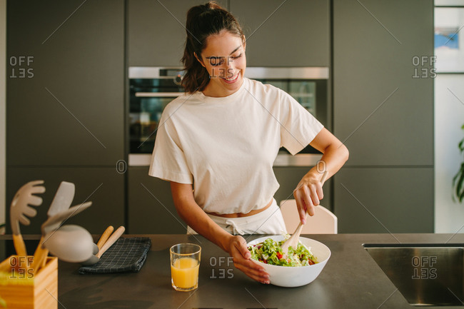 Peaceful female standing at table with bowl of vegetable salad and glass of orange juice at home