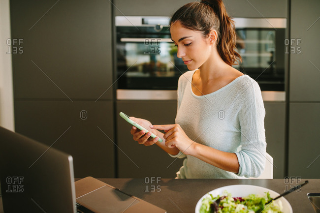 Young female remote worker in casual clothes checking messages on mobile phone while sitting at kitchen counter with laptop and bowl of salad