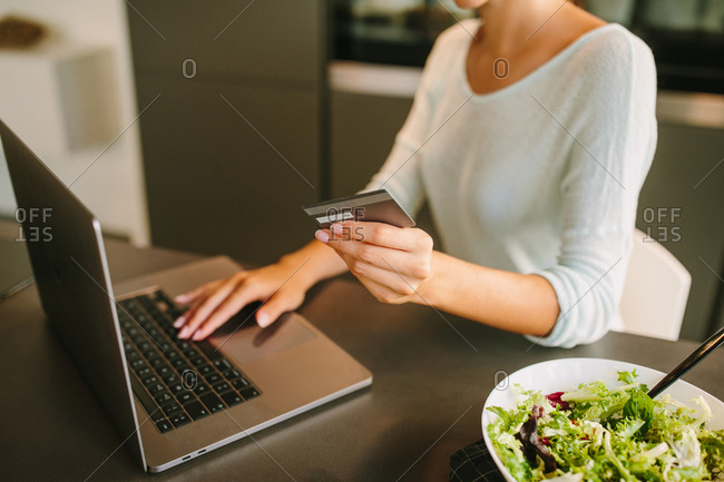 Unrecognizable young female with credit card in hand using laptop and making online order from internet shop while sitting in modern kitchen at home