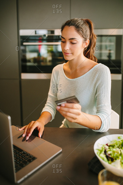 Positive young female with credit card in hand using laptop and making online order from internet shop while sitting in modern kitchen at home