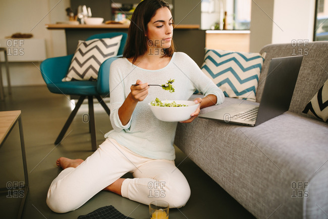 Young female in casual outfit sitting on floor and watching video on laptop while having healthy lunch with salad and cup of juice at home