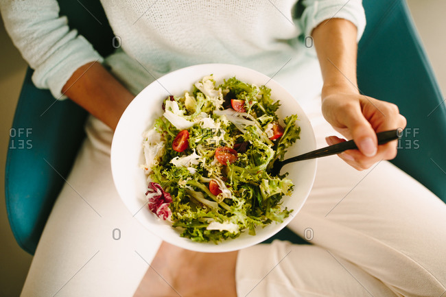 Top view of unrecognizable young female in casual wear sitting on chair and eating healthy vegetarian salad in modern home kitchen