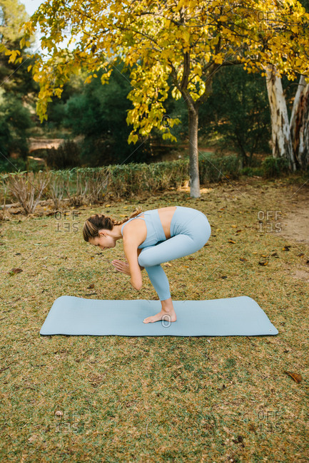 Full body side view of young slim female performing One Legged Chair pose during yoga session in park