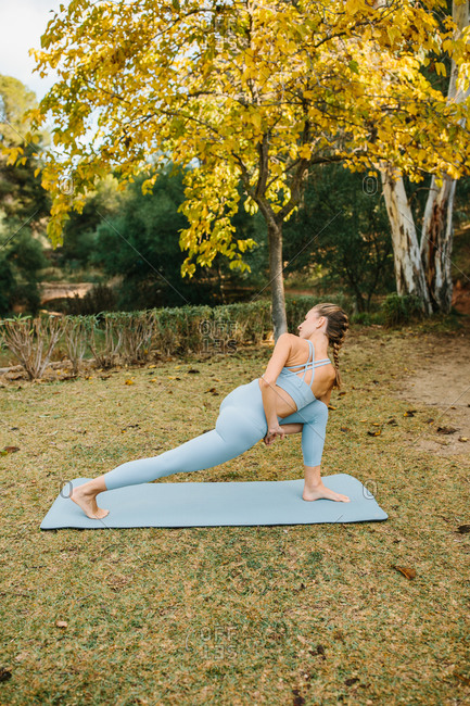 Full body side view of flexible slim female standing on mat and performing Bound Revolved Crescent Lunge pose while practicing yoga in park