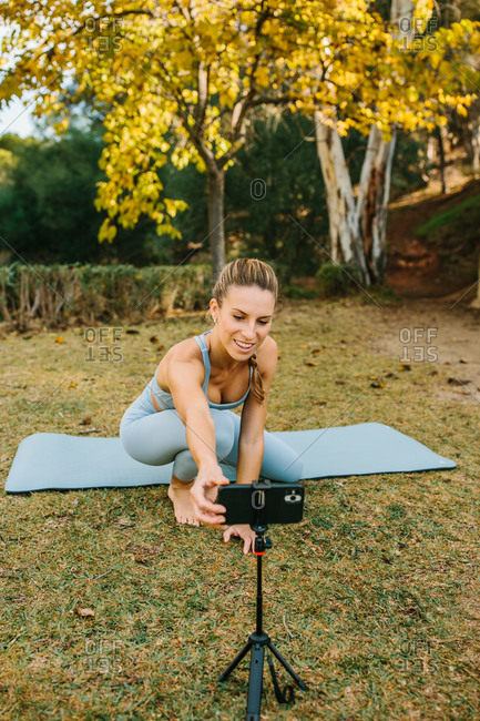 Positive young female yoga instructor setting smartphone on tripod while preparing for online yoga session in park