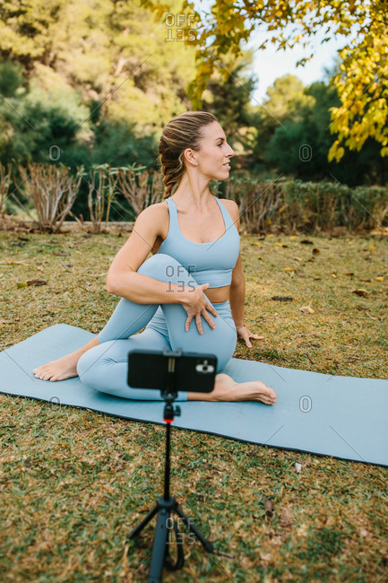 Flexible female practicing yoga and recording video on smartphone for blog while sitting in Ardha Matsyendrasana on mat in park