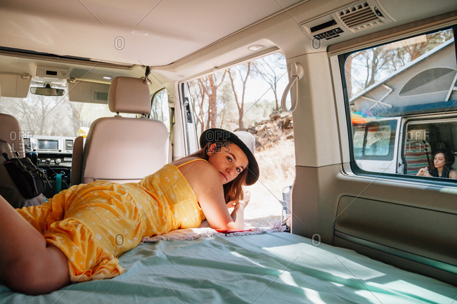 Side view of young female traveler in summer clothes lying in van and chilling on sunny day in woods during vacation while looking at camera