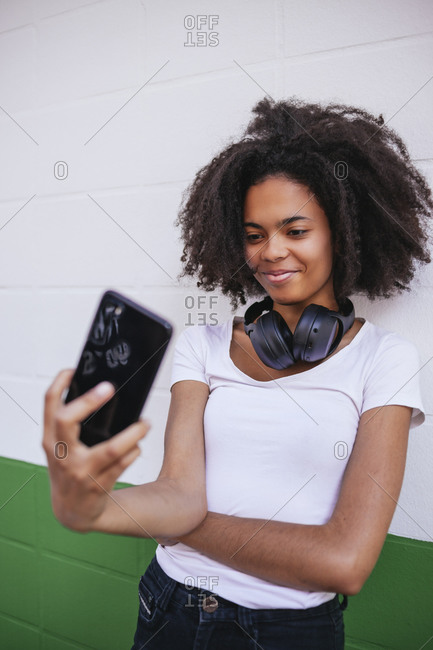 Charming African American female with headphones on neck leaning on building in city and taking selfie on smartphone for social media