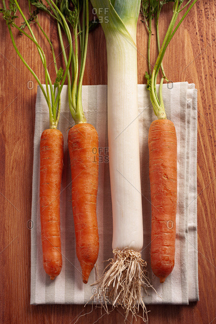 Top view composition with fresh raw orange carrots with stems and green leek placed on wooden cutting board
