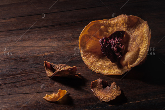 Still life chiaroscuro composition with dehydrated sliced sweet potato and beet arranged in shape of flower on wooden surface